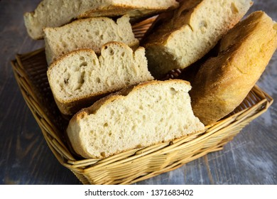 Italian bread of Focaccia Genovese type on display on a basket on a rustic wooden table, sliced in several squared pieces. The focaccia is a traditional oven baked flat bread, this one coming from Gen