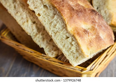 Italian bread of Focaccia Genovese type on display on a basket on a rustic wooden table, sliced in several squared pieces. The focaccia is a traditional oven baked flat bread,