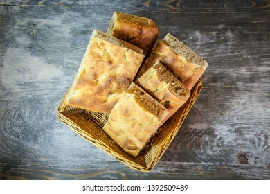 Italian bread of Focaccia Genovese type on a rustic wooden table, sliced in two squared pieces. The focaccia is a traditional oven baked flat bread, this one coming from Genoa, or Genova