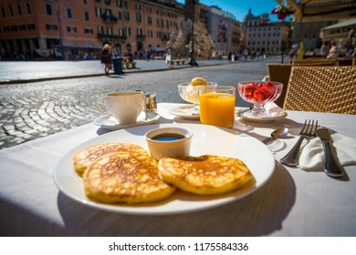 Italian breakfast including pancakes fruits and drinks on the background of Piazza Navona in Rome,Italy