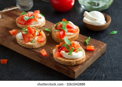 Italian bruschetta with chopped tomatoes, basil, mozzarella cheese and balsamic vinegar. Fresh homemade caprese bruschetta or crostini and ingredients on black background, copy space.