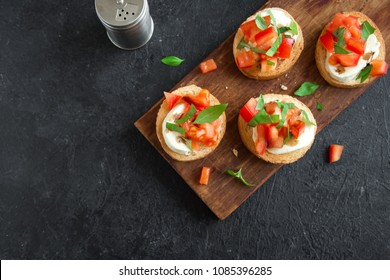 Italian bruschetta with chopped tomatoes, basil, mozzarella cheese and balsamic vinegar. Fresh homemade caprese bruschetta or crostini over black stone background, copy space.