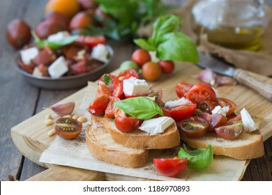 Italian bruschetta with chopped tomatoes, basil, feta cheese and olive oil. Fresh homemade caprese  or crostini over wood  background
