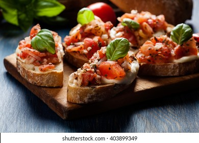 Italian bruschetta with roasted tomatoes, mozzarella cheese and herbs on a cutting board
