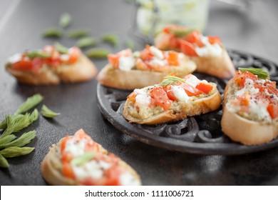 Italian bruschetta with spruce sprout pesto, tomatoes and mozzarella