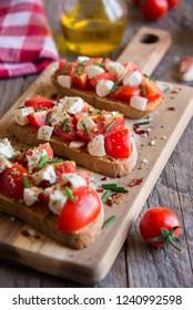 Italian bruschetta with tomatoes and mozzarella and herbs on dark background