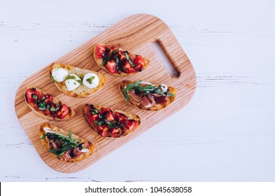 Italian bruschetta with tomatoes, Prosciutto di Parma, Mozzarella balls with pesto sauce, arugula and balsamic glasse on cutting board on white background. Mini sandwiches set. Top view. Copy space.