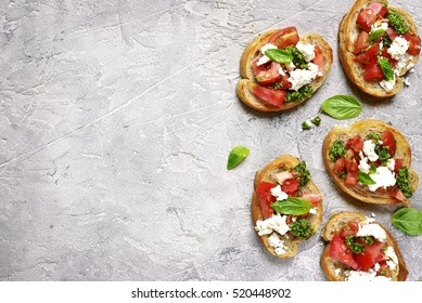 Italian bruschetta with tomatoes,feta and basil pesto on a grey concrete or stone background.Top view.