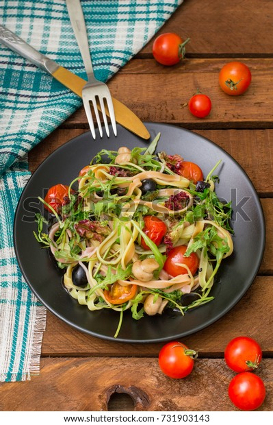 Italian bucatini with shrimp, arugula and cherry tomatoes. Wooden background. Top view. Close-up