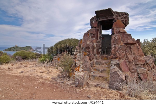 Italian bunker from WWII on Sardinia with sea and island in the back