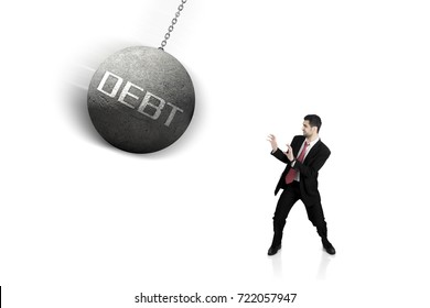 Italian businessman looks scared while standing near a wrecking ball with word of debt, isolated on white background