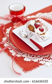Italian cake baba with a cream and strawberries in white and red plates and red cup with ribbon on napkin on wooden board