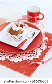 Italian cake baba with a cream and strawberries in white and red plates, red cup with ribbon on napkin on wooden board