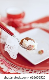 Italian cake with a cream and strawberries on spoon in red and white colors