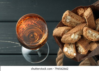 Italian cantucci biscuits and a glass of sweet Vin Santo wine over wooden background