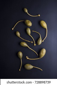 Italian caper berries with stems isolated on black background