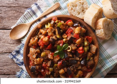 Italian Caponata with aubergines close-up in a wooden plate. horizontal view from above
