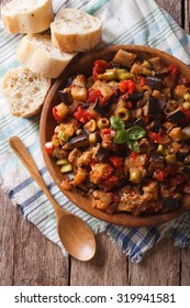 Italian Caponata with aubergines close-up in a wooden plate. vertical top view