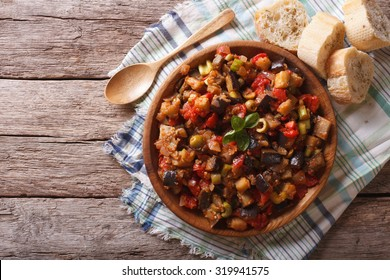 Italian Caponata with aubergines in a wooden plate. horizontal view from above