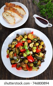 Italian Caponata with vegetables, green olives, capers, celery and herbs on white plate on dark wooden table with vinegar and bread on background, vertical view from above, close-up