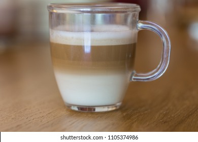 Italian Cappuccino coffee served in a clear glass with a nice thick foam on a wooden table