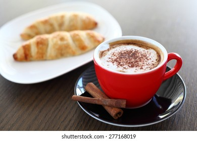 An italian cappuccino served with cocoa and croissant with intentional blurred background
