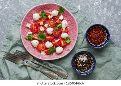 Italian caprese salad, cherry tomatoes, mozzarella and greens on a gray background. Top view, flat lay
