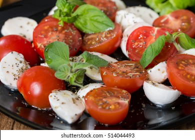 Italian Caprese salad with cherry tomatoes and baby mozzarella on black plate