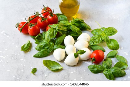 Italian caprese salad. Ingredients mozzarella buffalo, fresh basil, red tomatoes and olive oil. Italian cuisine, healthy lunch food. white stone background. selective focus, copy space