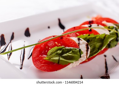 Italian Caprese salad. Mozzarella cheese, tomatoes and basil herb leaves. Balsamic vinegar arranged on white plate