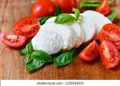 Italian Caprese salad: red tomatoes, fresh organic mozzarella and Basil, Italian cuisine