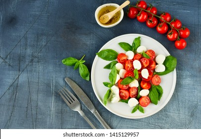 Italian Caprese salad: red tomatoes, fresh organic mozzarella and Basil, Italian cuisine. Healthy lunch. Top view on gray stone table.