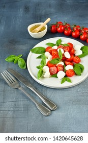 Italian Caprese salad: red tomatoes, fresh organic mozzarella and Basil, Italian cuisine. Healthy lunch. Top view on gray stone table