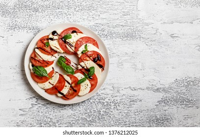 Italian caprese salad with ripe tomatoes, fresh basil and mozzarella cheese on grey stone background. Italian caprese salad in white plate with sliced tomatoes