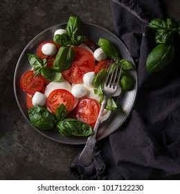 Italian caprese salad with sliced tomatoes, mozzarella cheese, basil, olive oil. Served in vintage metal plate with fork on textile napkin over dark metal background. Top view with space. Square image