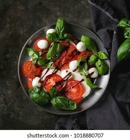 Italian caprese salad with sliced tomatoes, mozzarella cheese, basil, olive oil. Served in vintage metal plate on textile napkin over dark metal background. Top view. Rustic style. Square image