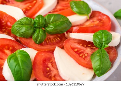 Italian caprese salad with sliced tomatoes, mozzarella cheese, basil, olive oil in a plate on gray concrete background. close up