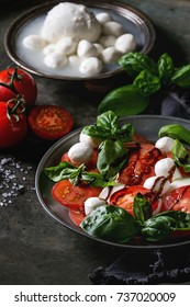 Italian caprese salad with sliced tomatoes, mozzarella cheese, basil, olive oil. Served in vintage metal plate with ingredients above over dark metal background. Close up. Rustic style
