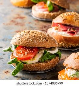Italian Caprese sandwiches with fresh tomatoes, mozzarella cheese and lamb's lettuce, multigrain bun. Healthy lunch concept with copy space