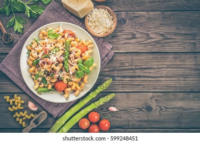 Italian cavatappi pasta with asparagus and tomatoes on wooden table, top view with copy space. Toned
