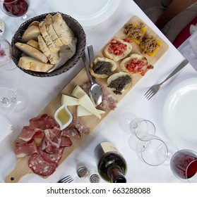 Italian cheese & appetizer board with bread and wine on white dinner table.