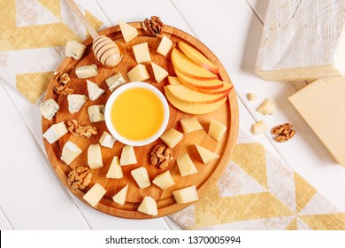 Italian Cheese Board Peach Gourmet Food Flat Lay. French Cheeseboard with Brie, Parmesan and Mozzarella Assorted Top Down View. Various Blue Cheddar, Gouda and Walnut Appetizer Dessert Platter Above