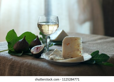 Italian cheeses, fresh figs and a glass of white wine on the rustic table with fig leaves