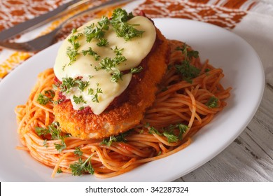 Italian chicken Parmigiana and pasta close up on a plate on the table. Horizontal