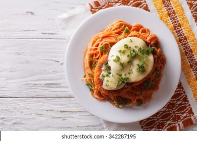 Italian chicken Parmigiana and pasta on a plate on the table. Horizontal top view