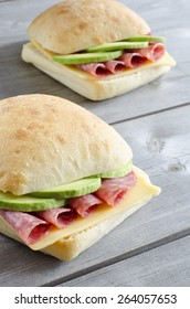 Italian ciabatta sandwich with salami, cheese and avocado on wooden background