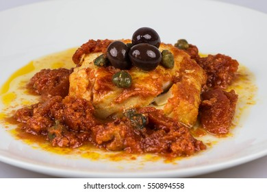 Italian codfish with black olives, cappers and tomato in a design plate, isolated on a white background