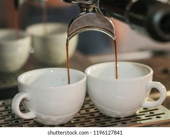 An Italian coffee machine pours fresh coffee into two white cups in a gourmet cafe