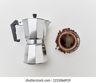 Italian coffee maker and the cup of fresh fragrant coffee beverage on a white background with copy space. Flat lay