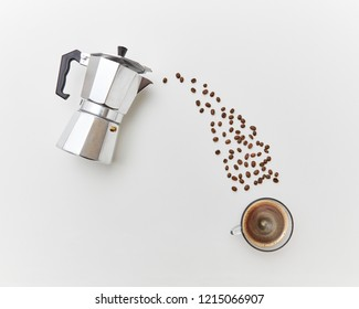 Italian coffee maker and fresh coffee beans coffee beans in the form of a drink stream on a white background with copy space. Concept of morning breakfast. Top view.